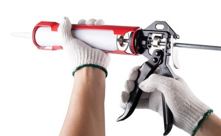 Worker applies silicone caulk gun isolated on white background  photo