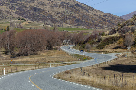 Asphalt road to the Arrowtown city, Southern Alps Mountain Valleys, New Zealand  photo