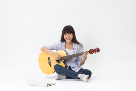 Beautiful Thai girl learning to play guitar online sitting on white background Standard-Bild
