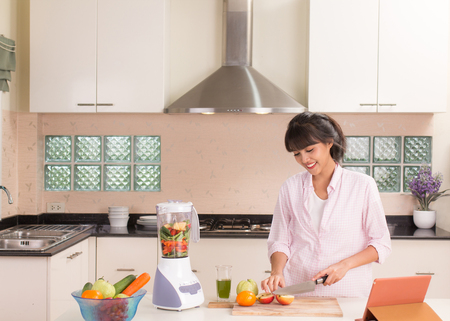 Beautiful girl preparing vegetable and fruit juice in modern style kitchen