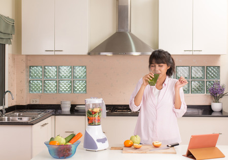 Beautiful Thai girl drinking fruit juice in modern style kitchen Banque d'images