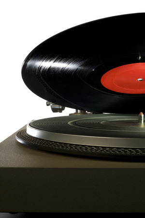 A vinyl record lowering onto a vintage record player  photo