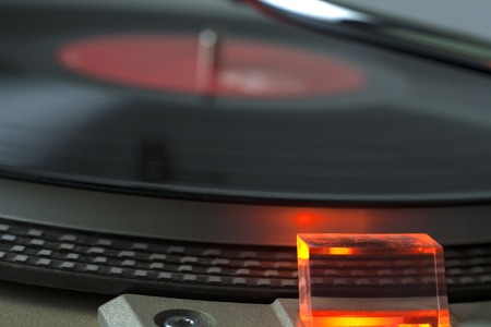 A close look at a vinyl record player that is turned on with the needle approaching the record  Stock fotó
