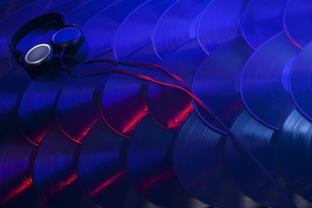 A pair of headphones sitting on several vinyl records overlapping in an organized array and lit with red, blue, purple and white lights  Stock fotó