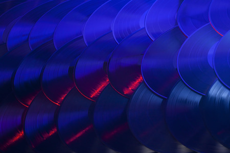 Several vinyl records overlapping in an organized array and lit with red, blue, purple and white lights  Stock fotó