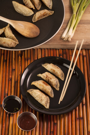 potstickers: Freshly cooked Chinese style pot stickers with soy sauce, pepper sauce and raw green onion  Four pot stickers are plated beside the cooking pan