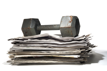 A stack of newspapers under a heavy dumbbell  The dumbbell is misused as it is rusted and employed as a paper weight  Stockfoto