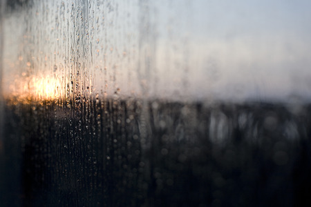 Rain on a window with the sun rising in the background