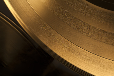 Close up view of a vinyl LP record that is lit with a golden light