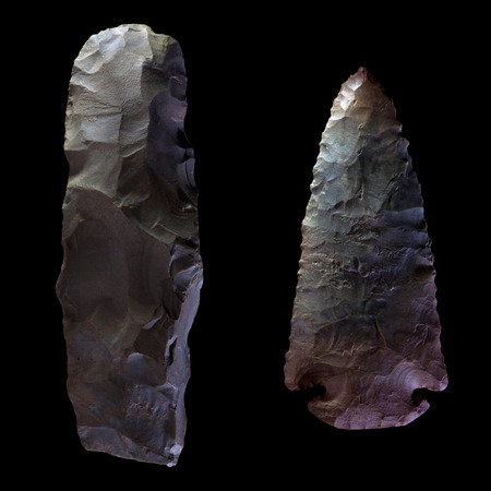 Two Arrowheads, one unfinished and one complete, isolated on black