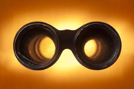 Looking through antique binoculars on a sunburst background. Stock fotó