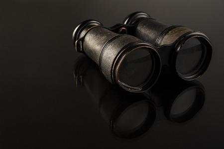 Antique binoculars sitting on a reflective dark surface.