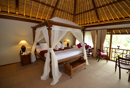 four poster bed: Bali hotel spa bedroom with four poster bed and mosquito nets