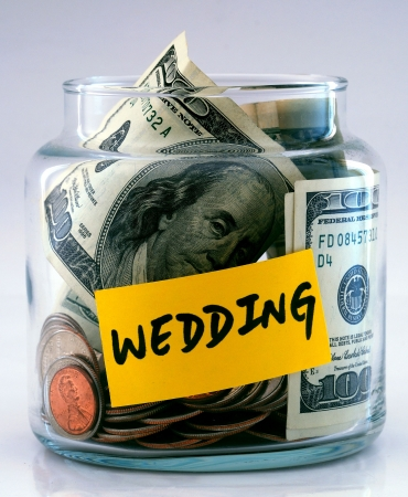 "A lot of money in a glass bottle labeled ""Wedding"" Stock Photo"