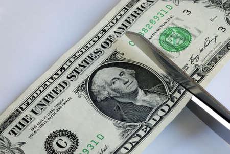 Cut the dollar bill with a scissors  photo
