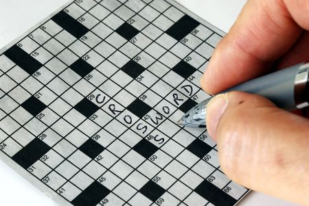 Solving the cross word puzzle from the newspaper Stock Photo - 6752094