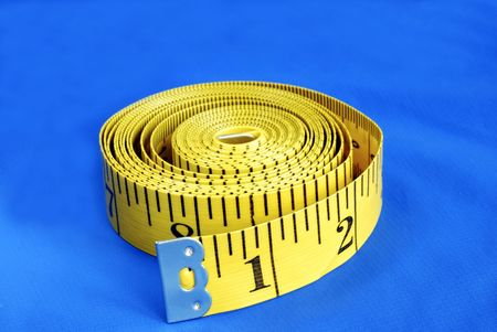 A coiled-like measuring tape isolated on blue background Stock Photo - 6752823