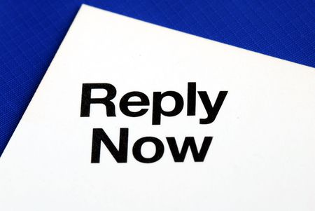 """""""Reply Now"""" from a business reply postcard isolated on blue Banque d'images"""