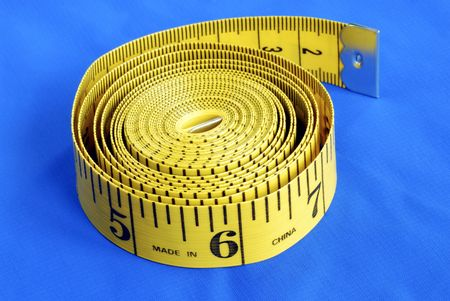 A coiled-like measuring tape isolated on blue background Stock Photo - 6752927