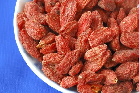 Goji berries also called wolfberries isolated on blue Stock Photo - 6752958
