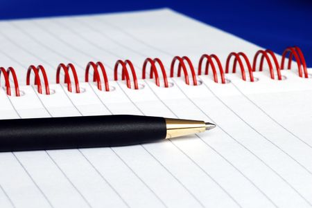 The spiral note pad with a pen isolated on blue Stock Photo - 6752158