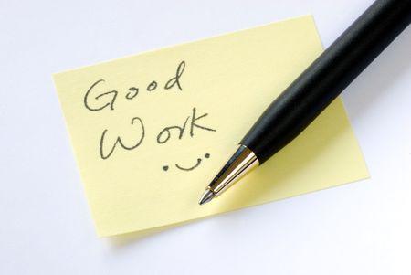 Escribir las palabras de buen trabajo sobre una nota adhesiva amarilla  Foto de archivo