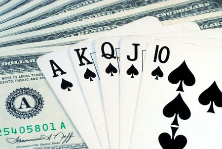 The Royal Flush on the top of some dollar bills Stock Photo