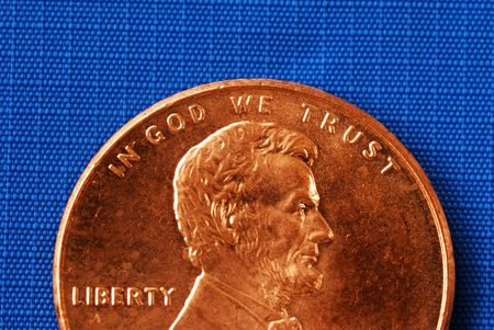 minted: In God We Trust from the penny isolated on blue