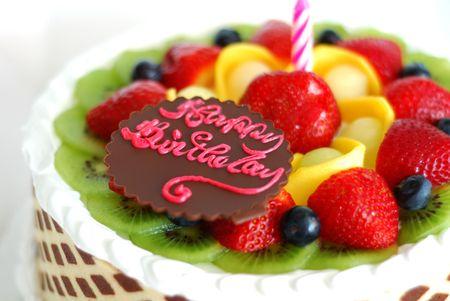 vejez feliz: Pastel de cumpleaños con frutas mixtas en la parte superior  Foto de archivo