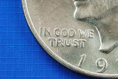In God We Trust from the dollar coin isolated on blue photo