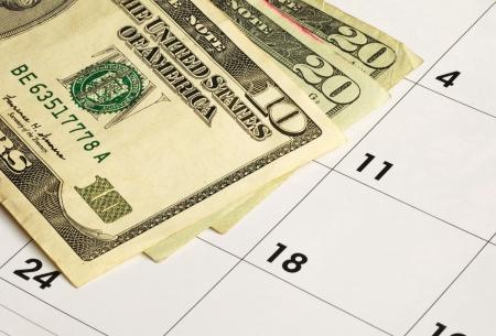 ファイナンシャル ・ プランニングのカレンダーの概念上でお金 写真素材