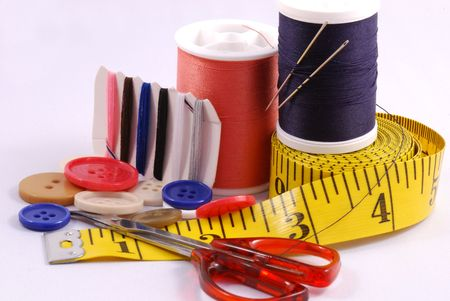 Some sewing tools such as threads, needles, buttons, and scissors photo