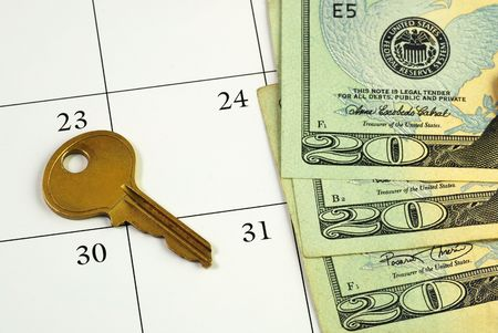 Key and money on a calendar concepts of paying the mortgage on time photo