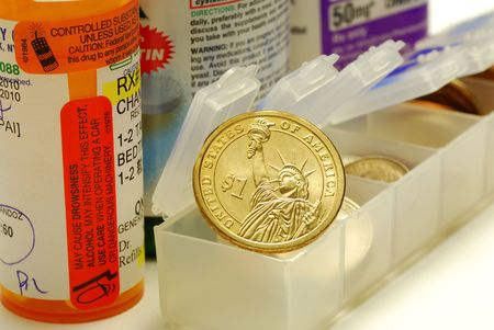 A gold coin on the medicine container concepts of rising medical cost photo