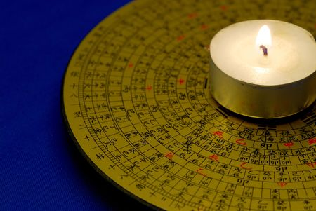 Chinese Feng Shui compass with the candle isolated on blue Stock Photo