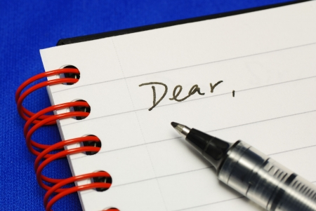 The word Dear with a pen concepts of writing a letter isolated on blue Stock Photo - 7652716