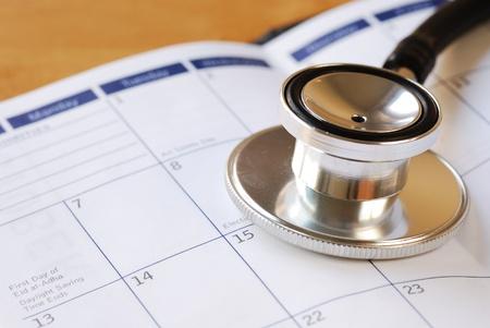 医療の予定のカレンダーの概念に聴診器 写真素材