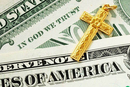A golden cross on the dollar bills concept of In God We Trust Stock Photo - 11532120