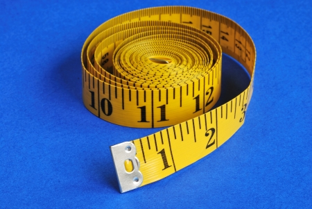 A coiled-like measuring tape isolated on blue background Stock Photo - 16324835