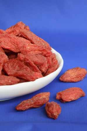 Goji berries also called wolfberries isolated on blue photo