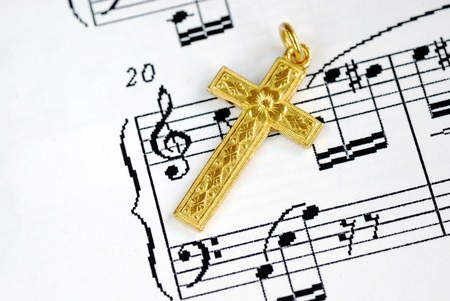A golden cross on the top of a music sheet concept of religion Stock Photo - 17710512
