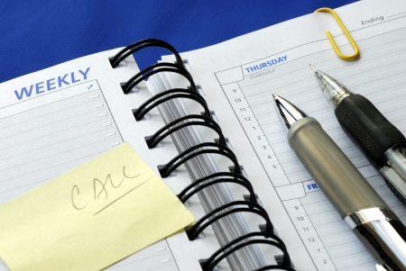 Write some notes on the day planner isolated on blue Stock Photo - 17710505