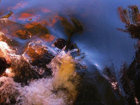 Detail of running water splashing against rocks