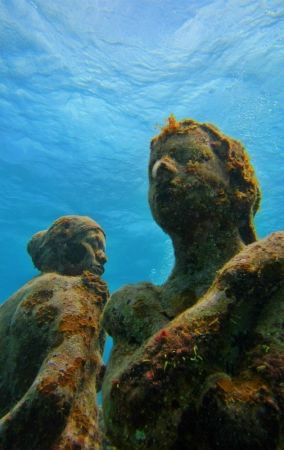 A unique perspective of statues with coral growing on them