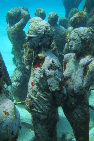 Statues that appear to be tourists on the sea bottom