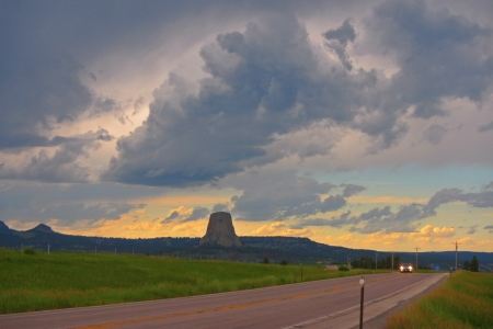 A view of Devil s Tower from ther highway as storm clouds move in at sunset