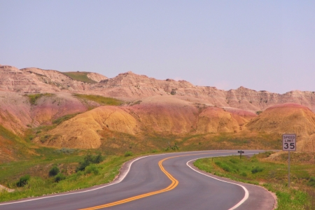 A highway winding through the Badlands of South Dakota highlights the beautiful landscape surrounding it  photo