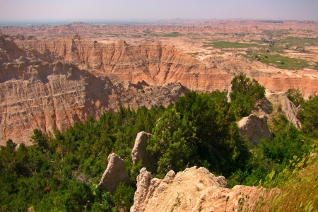The beautiful geological features of the South Dakota Badlands contrasted with the lush greens of some trees in the middle ground Stock Photo - 22116397