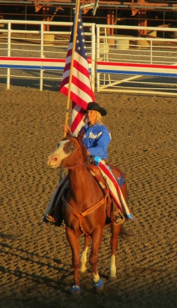 arena rodeo: Opening ceremony at the Cody night rodeo as rider on horseback comes into the arena with the American flag