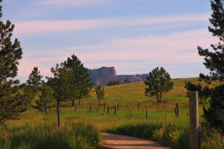 Crazy Horse memorial is seen in the far distance from an old dirt road  photo
